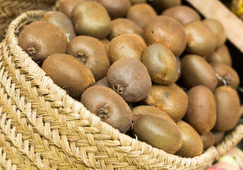 ripe kiwi in wicker baskets on counter market