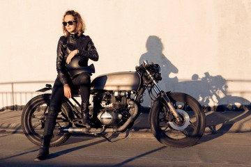 Sexy biker young woman in black trendy leather jacket sit on vintage custom made caferacer motorcycle. Urban roof parking, sunset in big city. Traveling and active hipster lifestyle. Girls power.