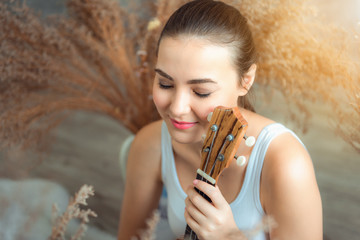 Close up portrait of young caucasian woman playing ukulele in living room, Leisure activities concept