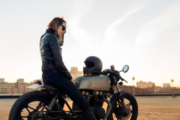 Sexy biker lady in black leather jacket sit on vintage custom caferacer motorbike and touch her hair. Urban roof parking, sunset in big city. Traveling and active hipster lifestyle. Girls power.