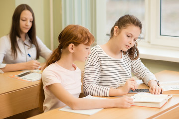 3 student girls are sitting at a Desk