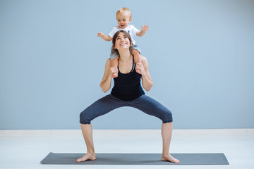 Cute european sporty mother playing with cute toddler baby boy. Little son sitting on his mother's shoulders at simple home interior. Motherhood, healthy lifestyle and people concept.