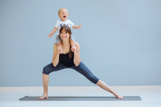 European sportive mother piggybacking her toddler baby son in fitness clothing on gray background. Lounge exercise. Motherhood, healthy lifestyle concept.