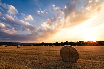 Dramatischer Sonnenuntergang auf einem Feld mit Strohballen