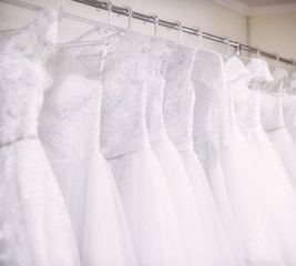Beautiful white wedding dresses hang on the counter in the store.