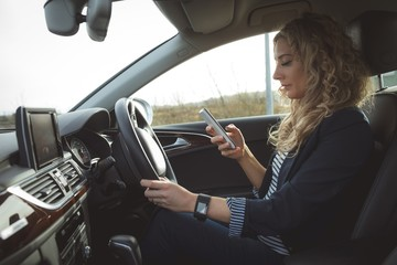 Female executive using mobile phone while driving in a car
