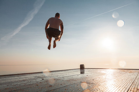 The guy is jumping from the pier. The sky and the sun. Summer. The man in flight.