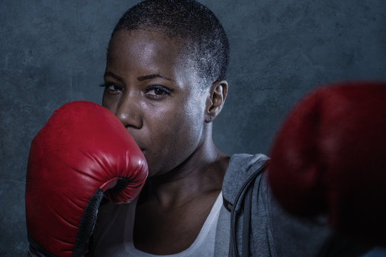 face portrait of young angry and defiant black afro American sport woman in boxing gloves training and posing as a dangerous fighter in fitness gym