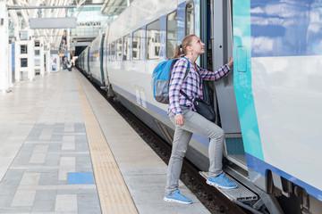 Young female tourist entering train. Rail travel