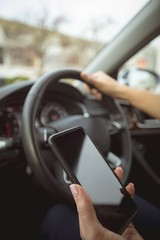 Female executive using mobile phone while driving a car