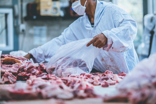 The raw meat packer and the slaughterer work in the slaughterhouse.