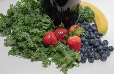 Blender with Blueberries, Strawberries, Bananas and Kale