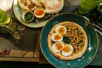 Middle eastern stile breakfast - hummus with eggs, pitas and dips