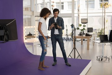 Photographer showing photos to fashion model on digital camera