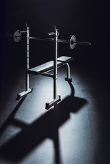 barbell with shadow on floor at gym, black background