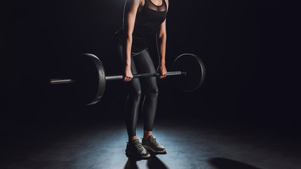 cropped image of female athlete working out with barbell at gym, black background