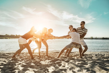 Friends funny tug of war on the beach under sunset sunlight in sun