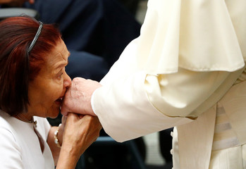 A woman kisses the hand of Pope Francis during the general audience at the Paul VI Hall in Vatican