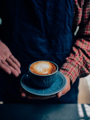 Close up man hands holding  coffee cup in coffee shop.