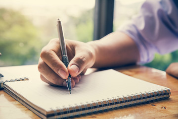 Close up image of man hand writing on notebook with wooden table background