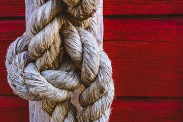Rustic rope knot on deep red wooden background