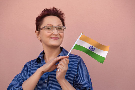 India flag. Woman holding Indian flag. Nice portrait of middle aged lady 40 50 years old with a national flag over pink wall background. Learn Hindi language. Visit India concept.