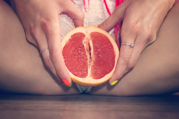 Close up of an grapefruit between woman's legs.
