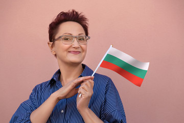 Bulgaria flag. Woman holding Bulgarian flag. Nice portrait of middle aged lady 40 50 years old with a national flag over pink wall background.Learn Bulgarian language. Visit Bulgaria concept.