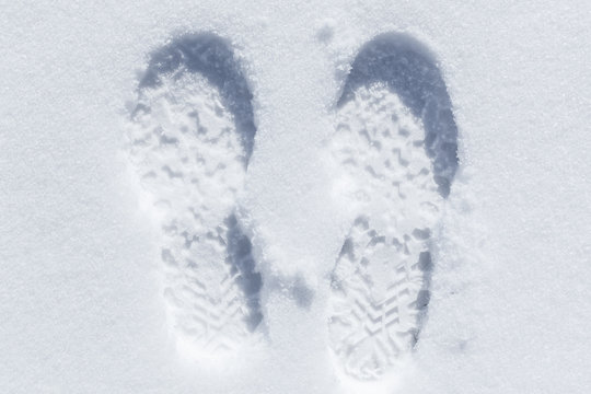 Feet imprint in white snow, close-up