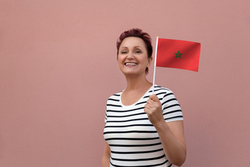 Morocco flag. Woman holding Moroccan flag. Nice portrait of middle aged lady 40 50 years old with a national flag over pink wall background.