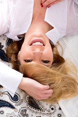 Sensual portrait of a beautiful happy young woman while lying on a bed and wearing a white shirt.