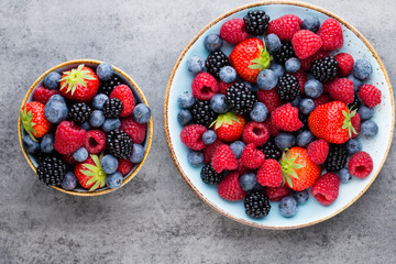 Fresh berry salad on blue dishes. Vintage wooden background.