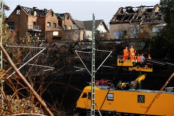 Burnt houses are seen in the background as workers of Deutsche Bahn (German Railways) repair the catenary of a German ICE high-speed train in Siegburg