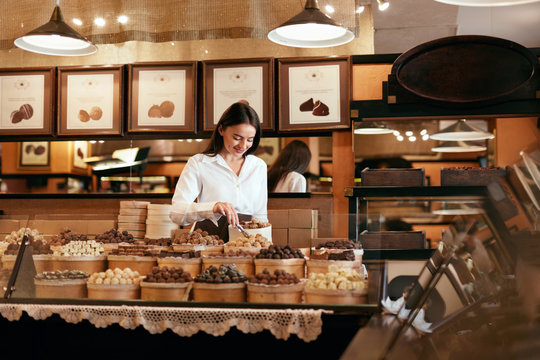 Confectionery. Woman Selling Chocolate Candies In Store