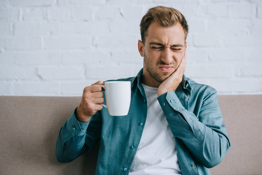 young man holding cup and suffering from toothache