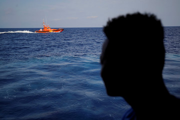 A migrant looks at Spanish rescue boat on board NGO Proactiva Open Arms rescue boat in central Mediterranean Sea