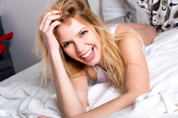 A beautiful smiling young woman lying on a bed in a white tank top.