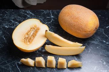 Whole, half and sliced honeydew melon fruit on dark marble background.