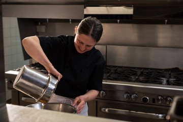 Chef pouring oil into a container