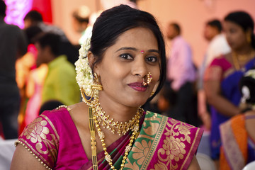 Woman dressed in Indian attire at wedding ceremony looking at camera, Pune