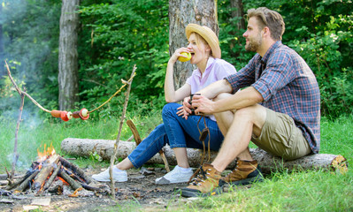 Couple romantic date near bonfire in forest. Couple relaxing sit on log having snacks. Pleasant picnic or romantic date nature background. Hike picnic date. Family enjoy romantic weekend in nature