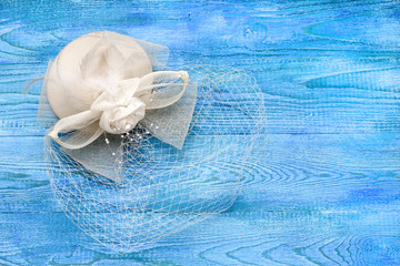 A small white hat with a veil on a blue wooden table, a top view and a copy space. Decoration for the bride.