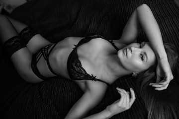 Sensual photo of a beautiful woman lying on a bed and posing in a black lingerie.