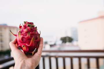 Close up food image of dragon fruit in woman's hand. Travel inspiration photo with a small depth of field. Blur background with copyspace for design
