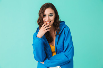 Photo of joyous pretty woman 20s wearing raincoat or jacket smiling at camera, isolated over blue background