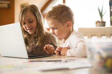 Children using laptop together in kitchen