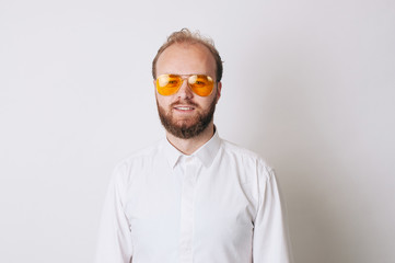 Portrait of young bearded man wearing yellow sunglasses and looking confident at the camera
