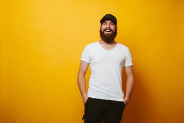 Portrait of young smiling bearded man wearing white t-shirt and black cap