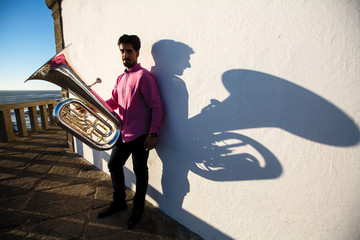 Man play Tuba near the white wall the shadow of the tool.