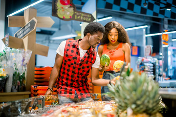 Young african couple in casual clothes choosing vegetables and fruits in grocery department of the supermarket, man is holding shopping basket